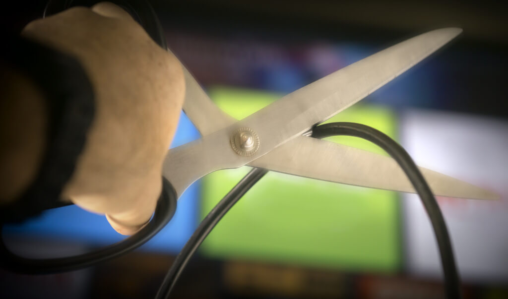 Hand holding scissors cutting the cable cord
