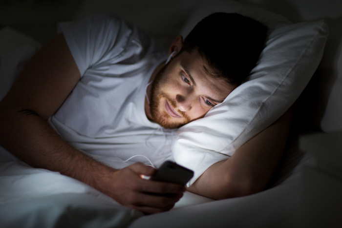 Man with a smartphone in bed