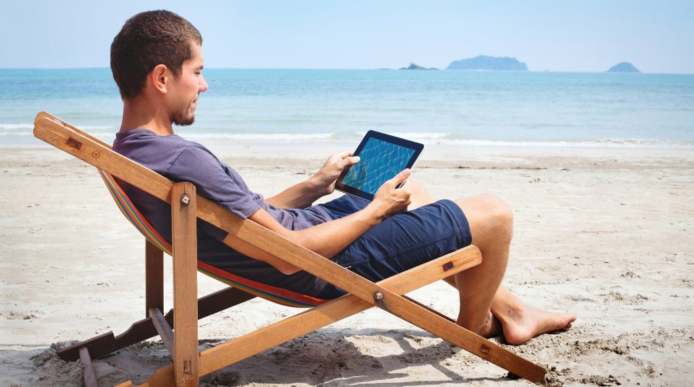 Man watching a tablet on the beach vacation