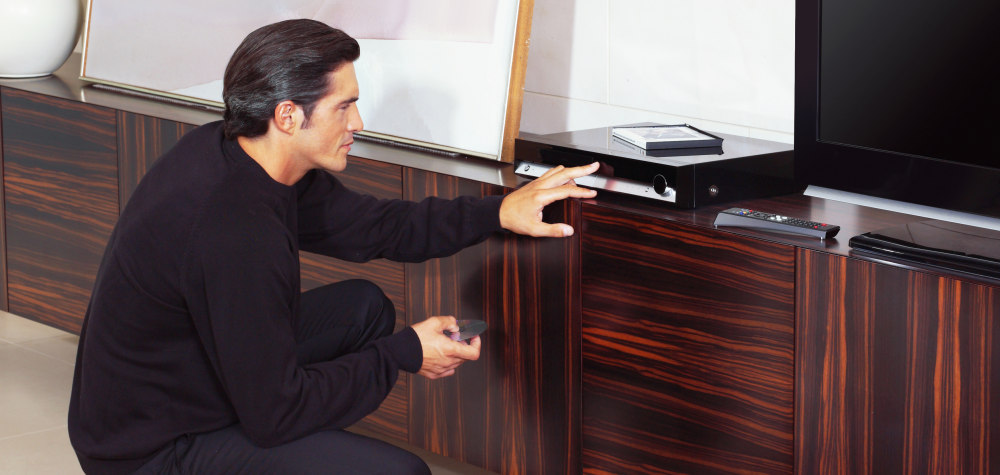 Man with blu-ray player living room 1000