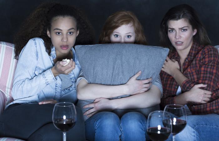 Three women watching scary TV horror film