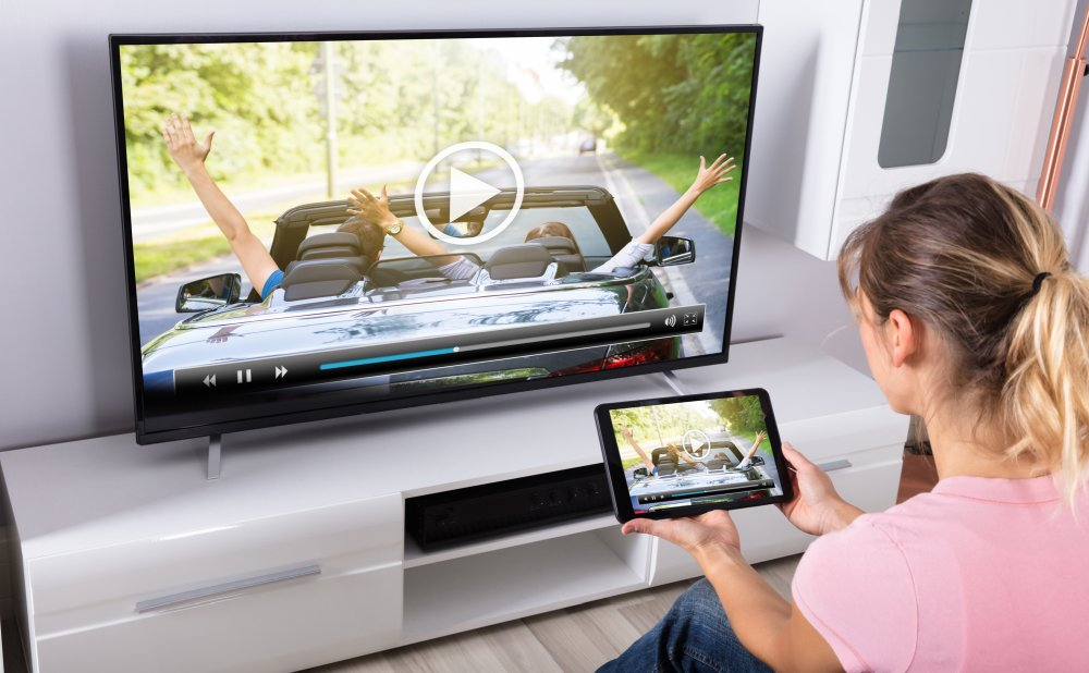 woman watching streaming on tv and tablet