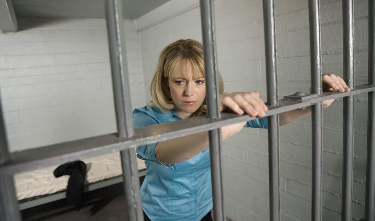Woman in prison behind bars 1200