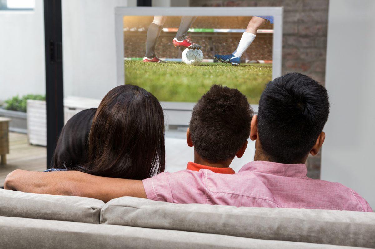 family watching football on tv sofa