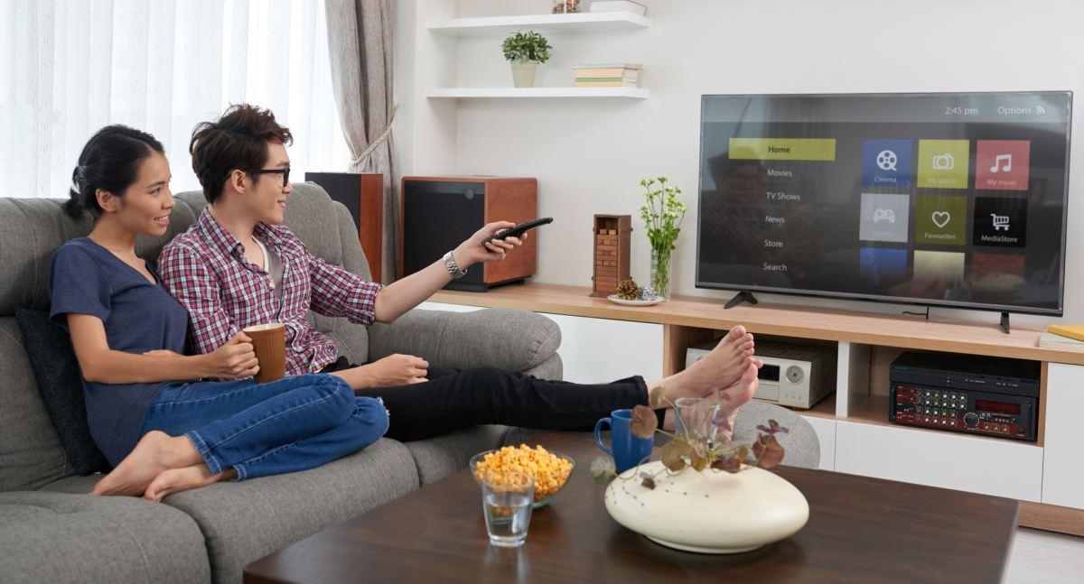 Couple watching smart TV in living room 1200