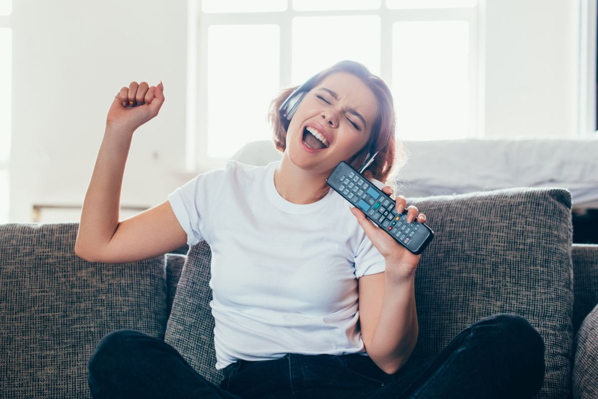 woman singing with TV remote 1200
